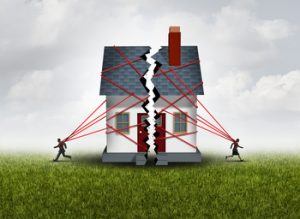 Broken family after a bitter divorce settlement and separation with a couple in a bad relationship breaking a house apart showing the concept of a marriage dispute and dividing assets with 3D illustration elements.